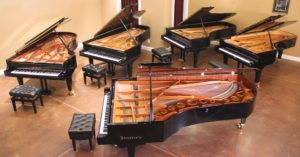 Overhead view of 5 concert grand pianos in recital hall