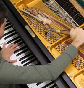 Overhead view of piano technician tuning a piano